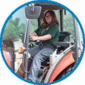 Photo of Ranger Edith sat in a tractor in a blue circle